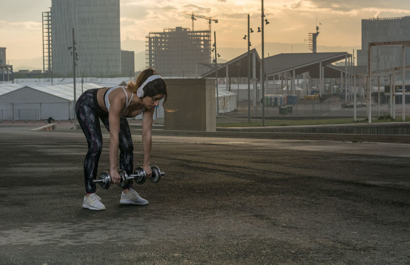 Woman Listening Music While Lifting Dumbbells In City During Sunset