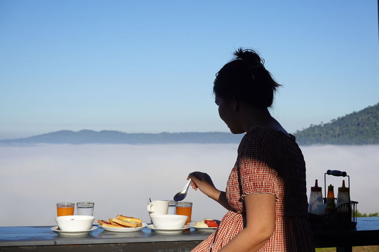 Woman with coffee cup against sky