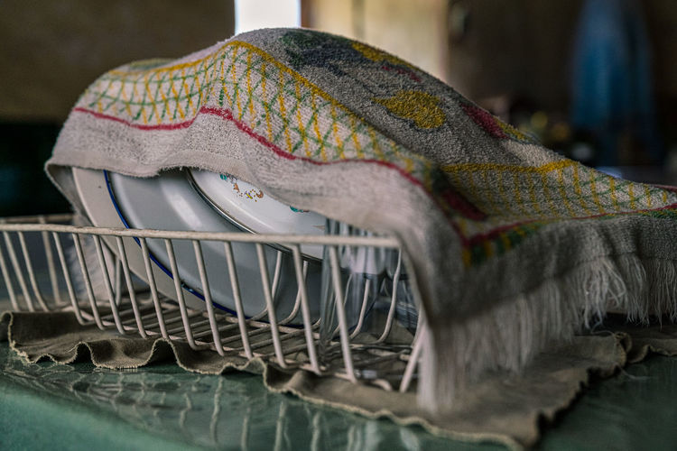 Close-up of dishes in dish rack covered by dish cloth