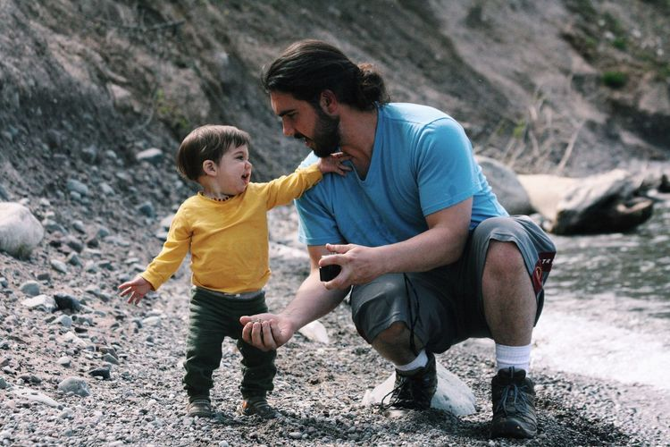 Cute boy playing with father