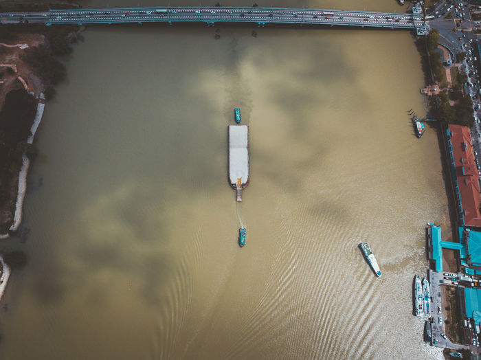 Aerial view of ships sailing in river at city