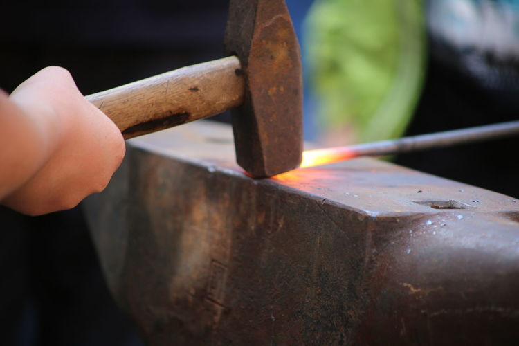 Cropped Hand Of Worker Hammering Metal On Anvil At Factory