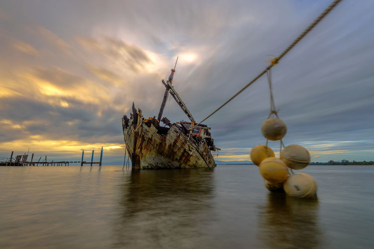 Shipwreck By Sea Against Sky During Sunset