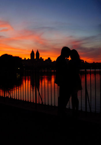 Silhouette couple standing by railing against sky during sunset