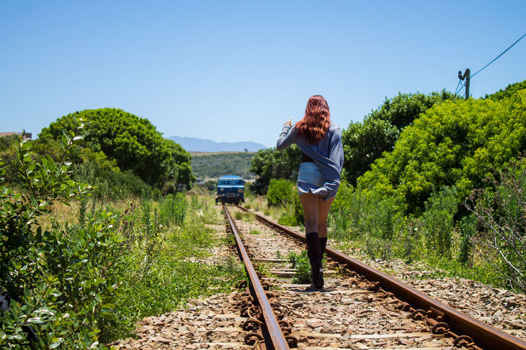 Woman standing by railroad tracks against sky