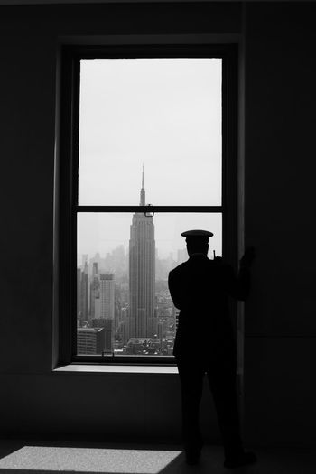 Rear view of policeman looking through window
