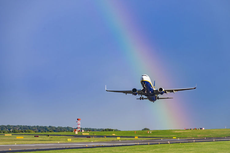 Airplane taking off against rainbow in sky