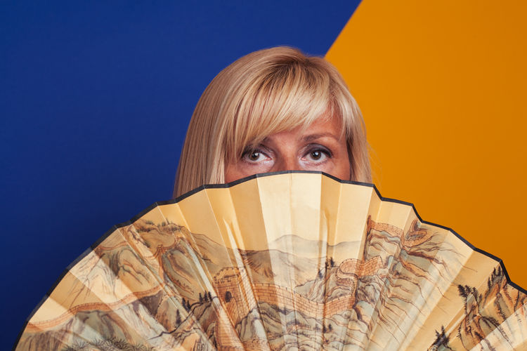 Portrait Of Woman Covering Face With Folding Fan