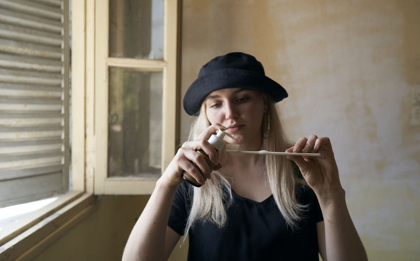 Portrait of young woman holding hat at home