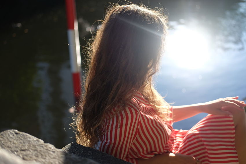 Summer by the river Adult Casual Clothing Day Hair Hairstyle Lake Leisure Activity Lens Flare Lifestyles Nature One Person Outdoors Real People Rear View Sitting Striped Sunlight Water Women