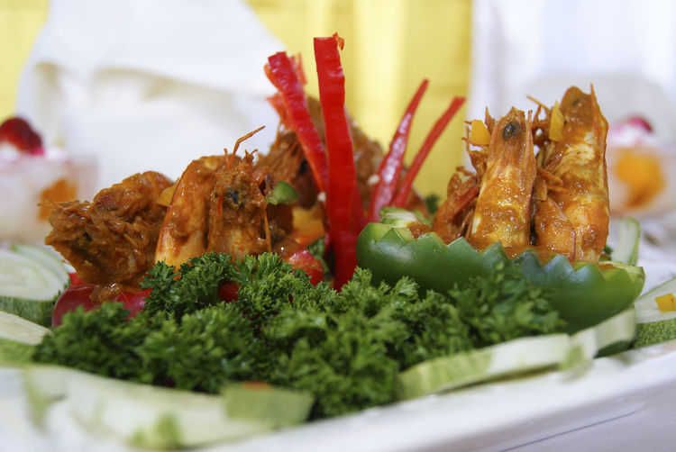 Close-up of prawns garnish with sliced cucumber on table