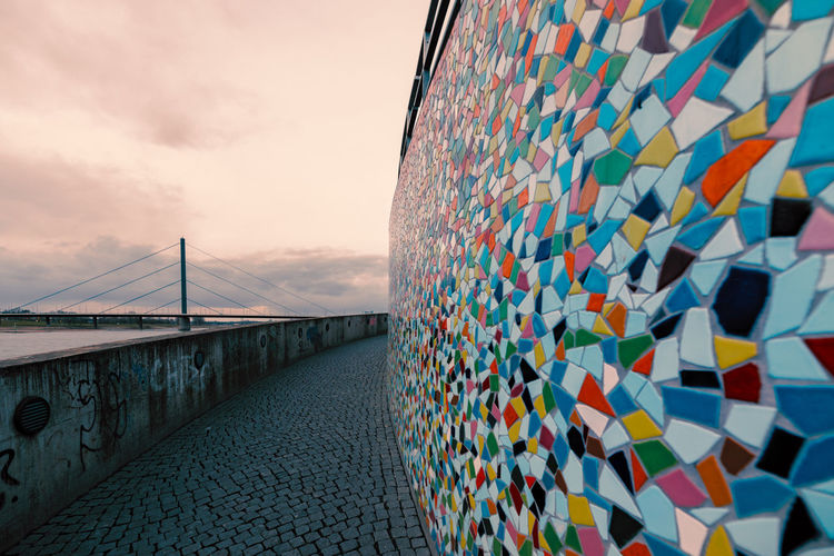 Duesseldorf, GERMANY - February 09, 2019: Colorful wall mosaik contrasts with dull grey winter light Built Structure Sky Bridge Architecture Cloud - Sky Bridge - Man Made Structure Connection Nature No People Building Exterior Wall - Building Feature Outdoors Pattern Multi Colored Day Travel Destinations Focus On Foreground City Transportation Art And Craft