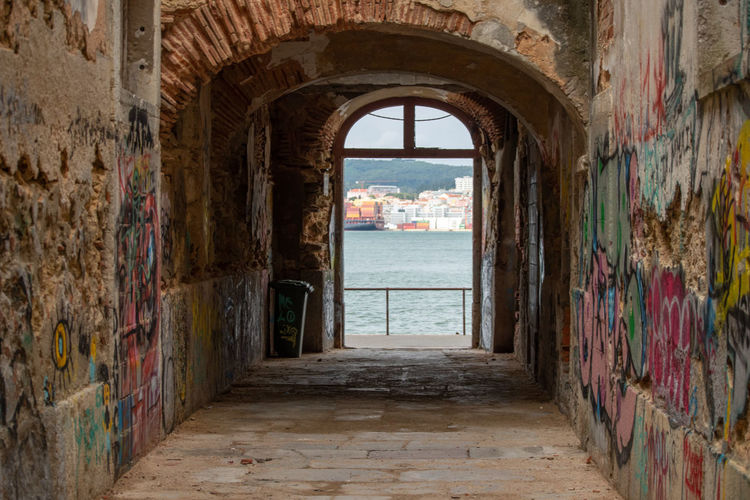 corridor of building Alley Arcade Arch Arched Architecture Building Building Exterior Built Structure City Day Direction History No People Old Outdoors The Past The Way Forward Travel Destinations Wall Wall - Building Feature Window