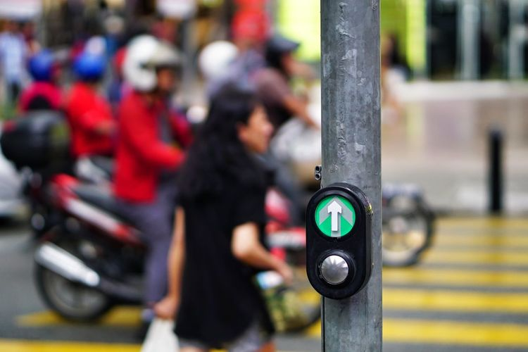 Close-up of button with arrow sign and people on road