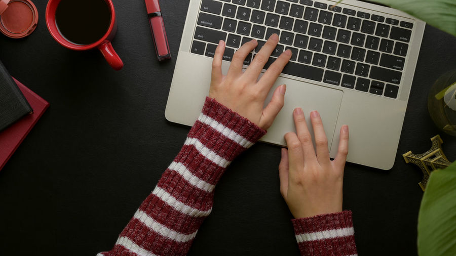 Cropped hands using laptop at desk