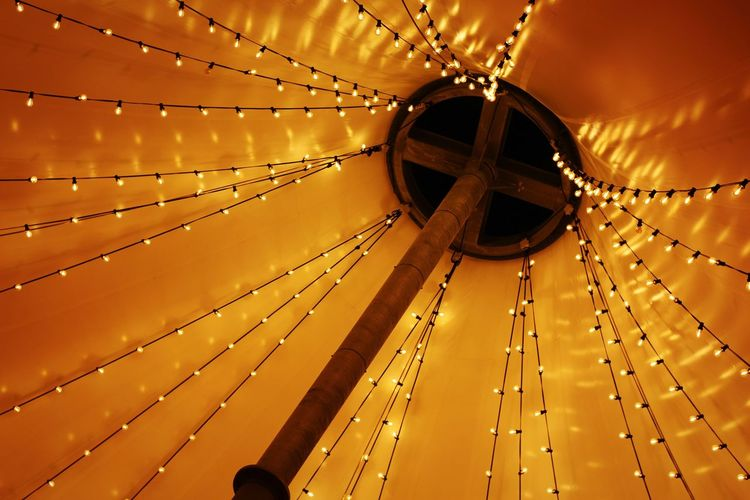 Low angle view of illuminated string lights hanging on ceiling in tent