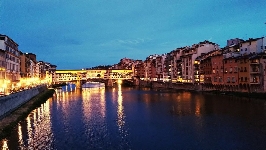 Bridge over river by illuminated buildings against blue sky