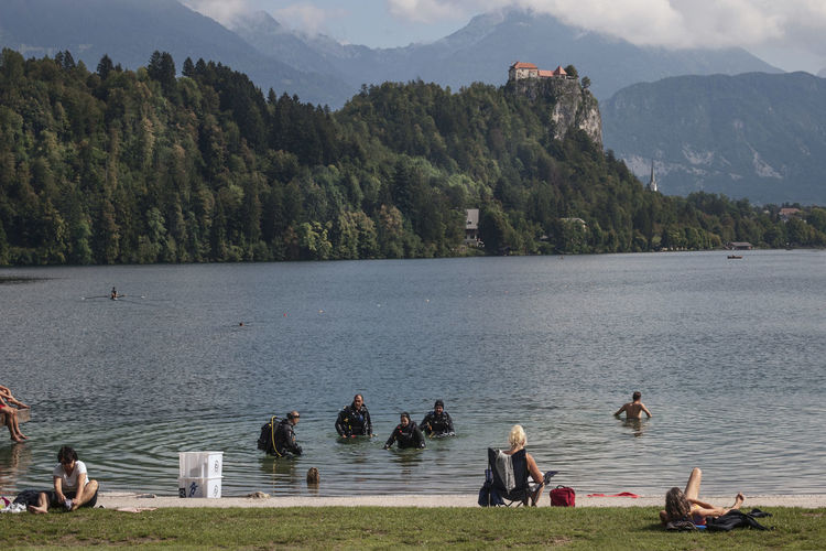 People by lake against mountain