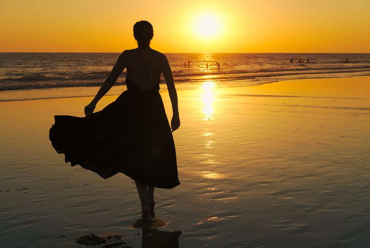 Silhouette woman walking at beach against clear orange sky