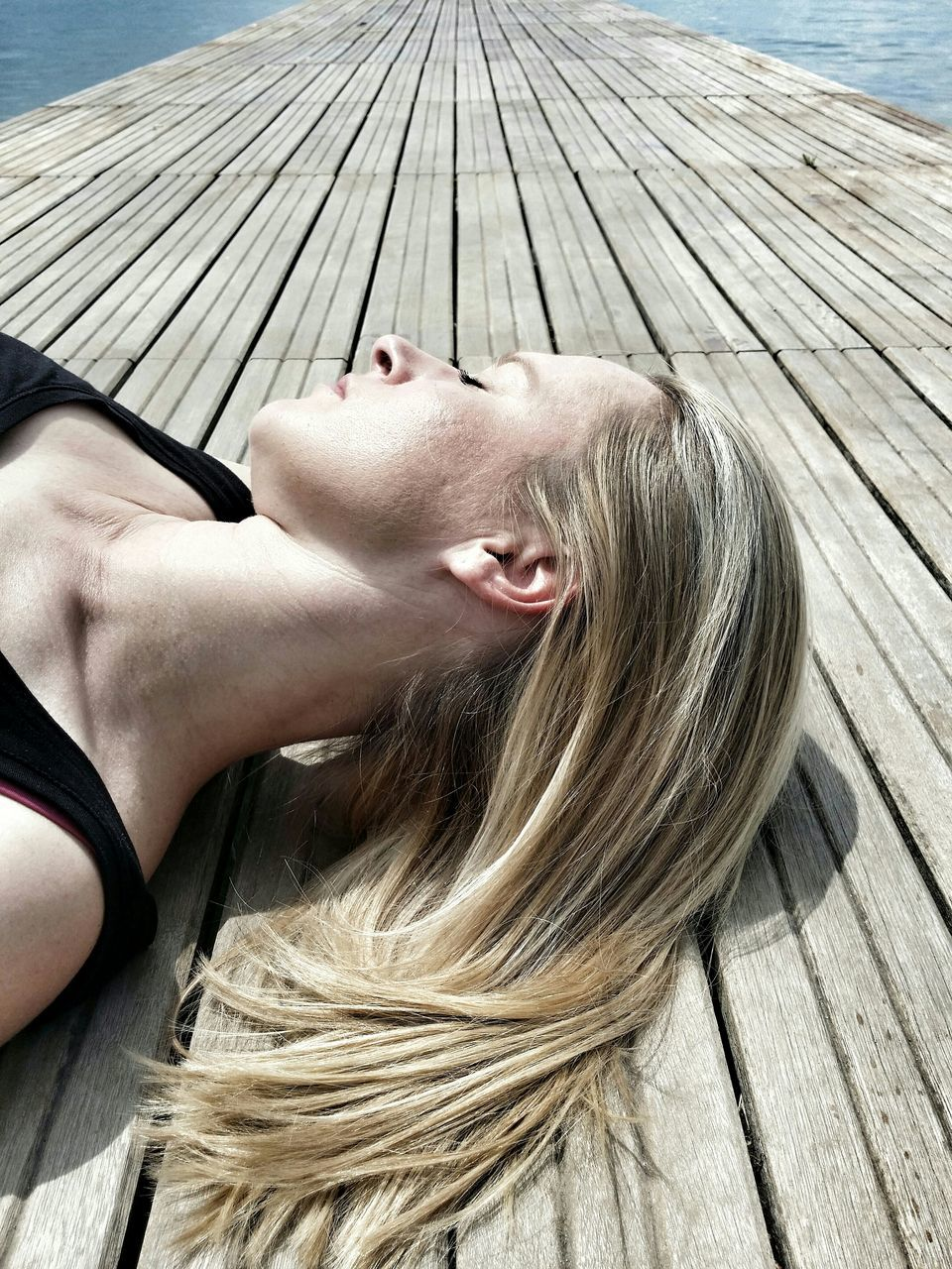 Close-Up Of Woman Relaxing On Pier