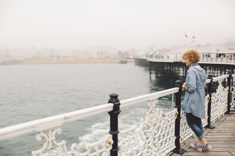 Full Length Of Young Woman Standing By Railing On Brighton Pier