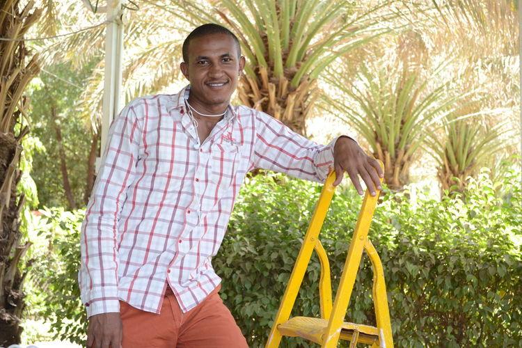 Portrait of smiling man standing on ladder against plants