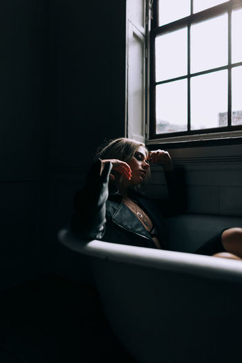 Bathroom Bathtub Beautiful Woman Contemplation Dark Day Domestic Bathroom Domestic Room Headshot Home Indoors  Leisure Activity Lifestyles One Person Portrait Real People Relaxation Side View Sitting Window Young Adult