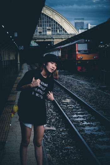 Young woman with backpack standing on railroad station platform