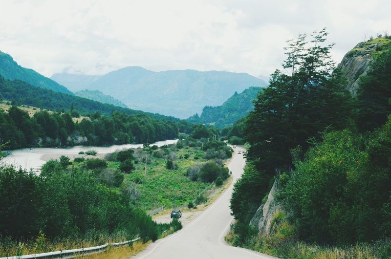 Scenic view of mountains by river against sky