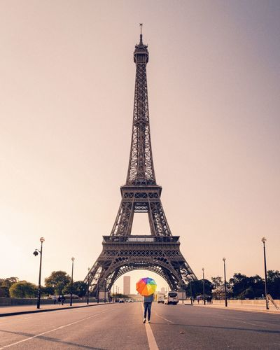 Person With Colorful Umbrella Standing Against Eiffel Tower In City Against Sky