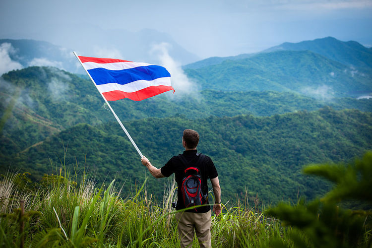 Man With Flag Standing On Field Against Mountains