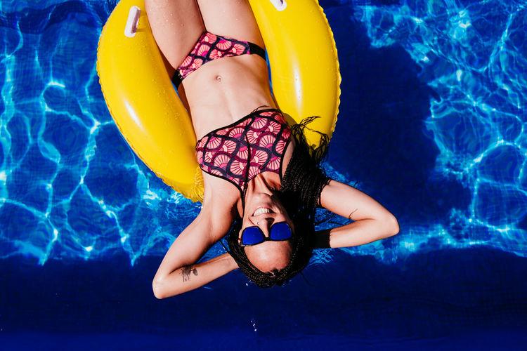Midsection of woman in bikini swimming pool