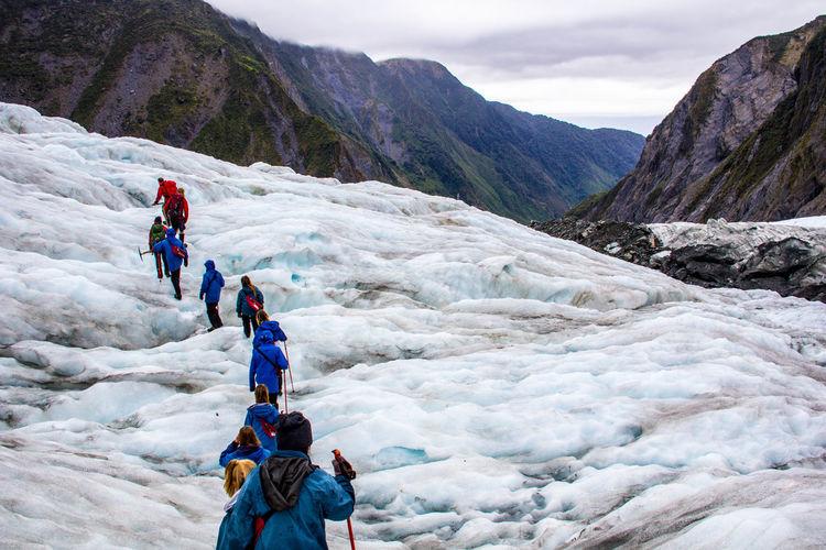 People walking on mountain during winter