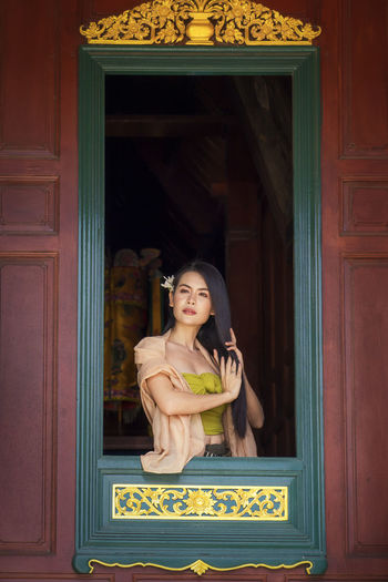 asian girl wearing thai traditional dress hand holding hair on window. looking at side.