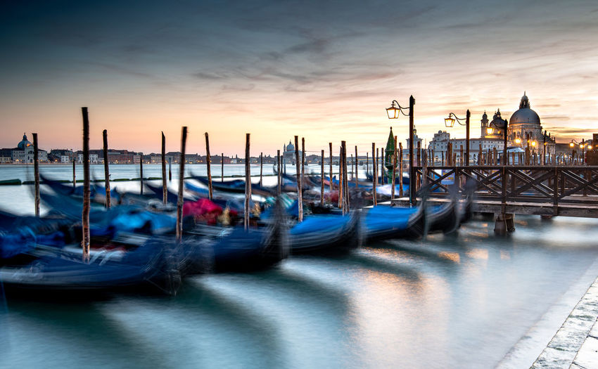 Boats moored in canal at sunset in venice, italy