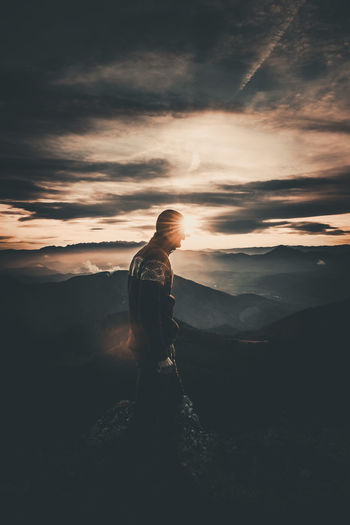 Man standing on mountain against sky during sunset
