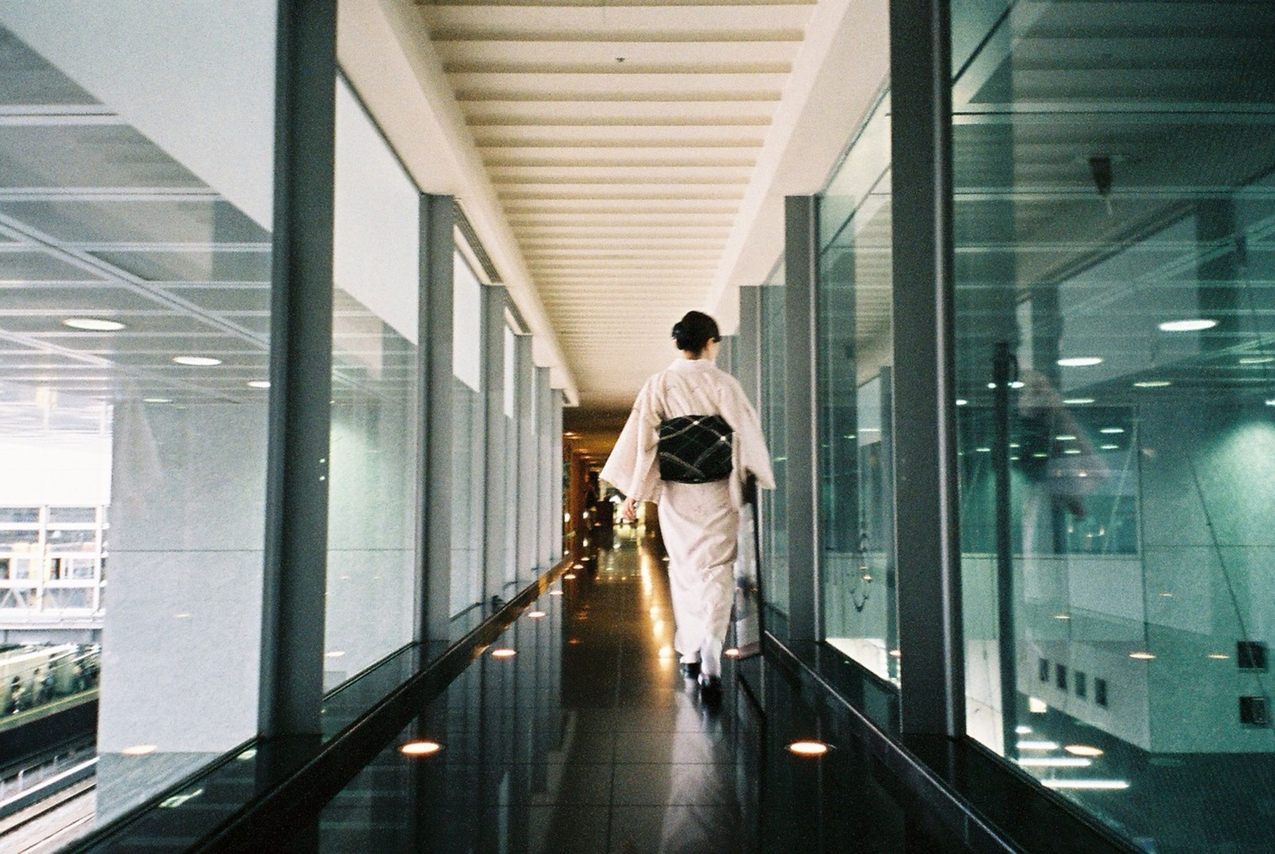 indoors, lifestyles, architecture, full length, built structure, reflection, standing, corridor, rear view, leisure activity, casual clothing, young adult, walking, person, modern, window, ceiling, young women