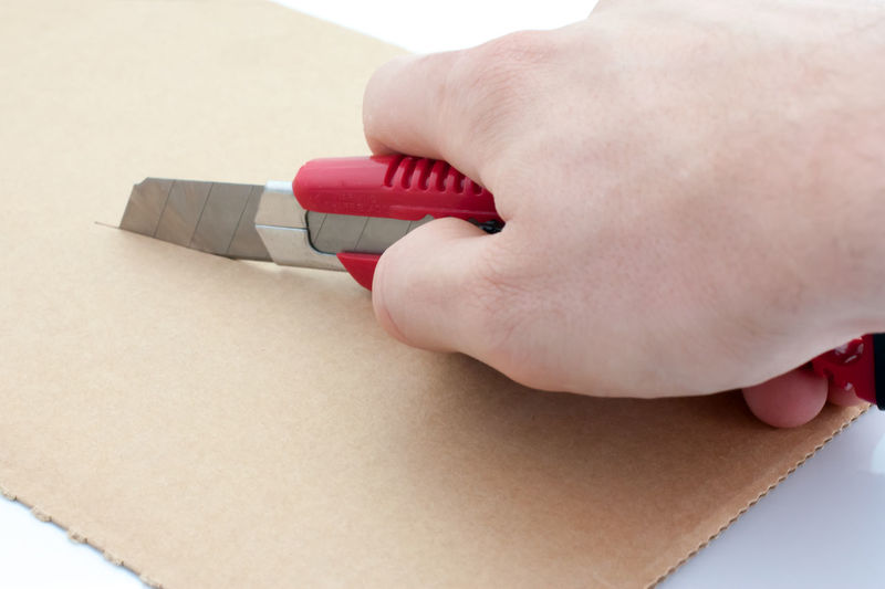 Close-up of hand cutting brown paper with utility knife on table