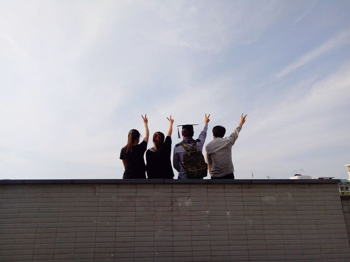 Rear view of friends gesturing peace sign on roof against sky