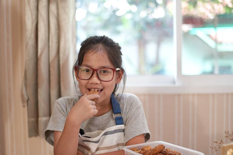 Portrait of smiling girl eating food at home