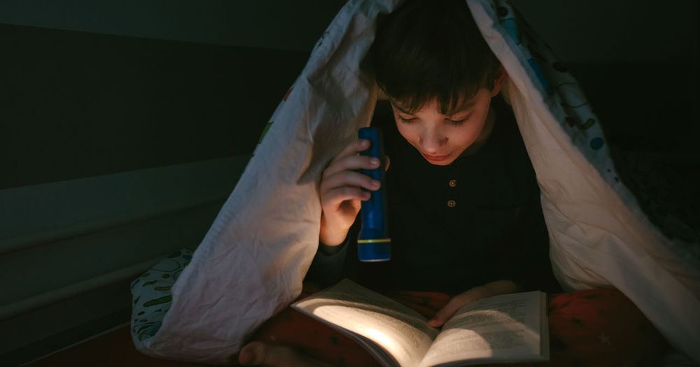 Boy reading book in darkroom at home