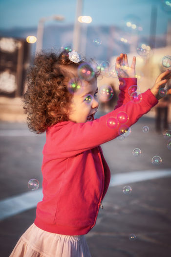 Side view of happy girl playing bubbles on road