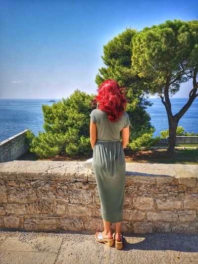 Rear view of redhead woman standing on footpath near sea against blue sky