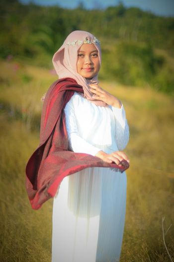 Portrait of bride wearing hijab while standing on field
