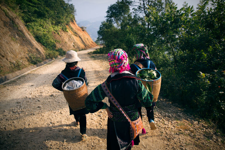 Rear View Of Women Carrying Baskets While Walking On Dirt Road