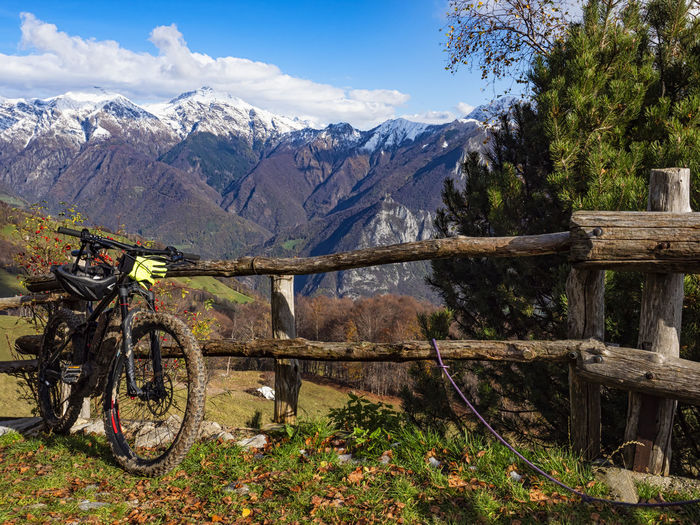 Bicycle by trees on mountains against sky