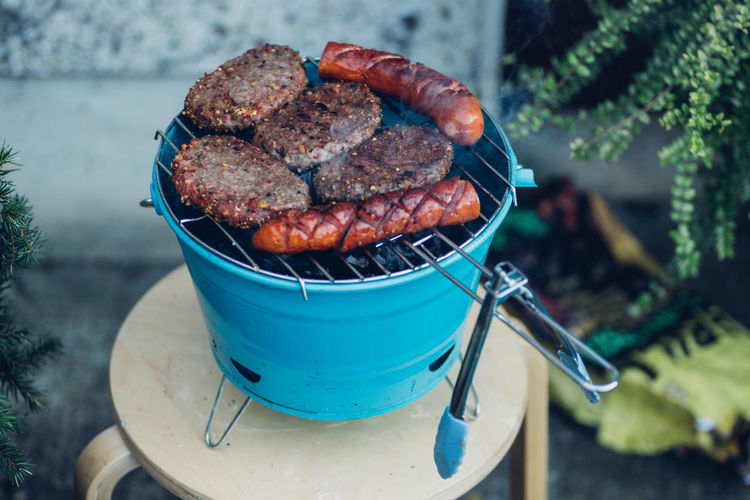 A small portable barbecue with sausages and burgers Barbecue BBQ Bbq Clamp Burned Cooking Food Food And Drink Grill Grilled Grilled Meat High Angle View Hot Food Meat No People Outdoors Portable Barbecue Preparation  Ready-to-eat Roast Beef Roasting Meats Sausage Sausages Smokey Tasteful Tasty Food