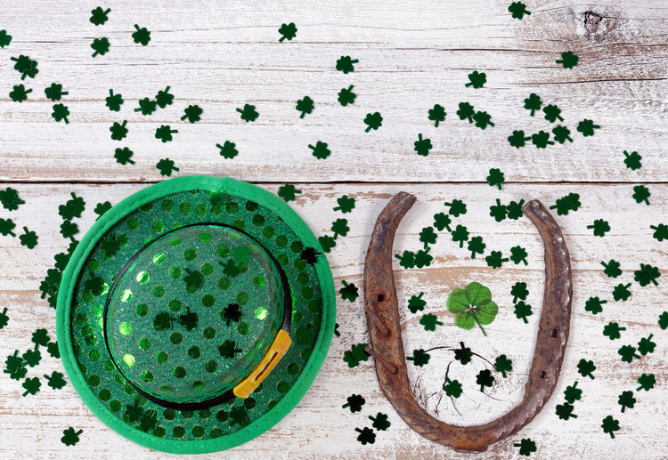 Real four leaf clover in the middle of rusty horseshoe with hat and shiny clovers on rustic wooden boards in overhead view Clover Four Leaf Clovers 🍀 Green Color Hat Holiday Horseshoe Luck St Patrick's Day Irish St Patrick