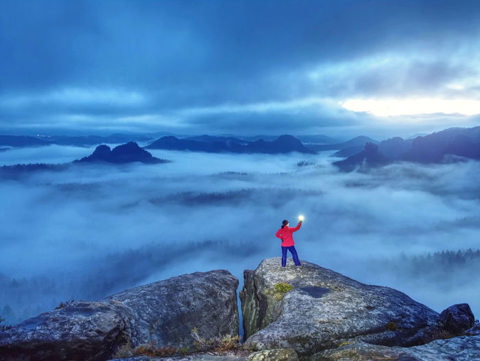 Beautiful lost woman hold in hands bright shining lamp on mountain summit. alone woman lightning