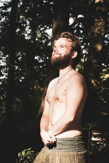 Young shirtless man looking away in forest